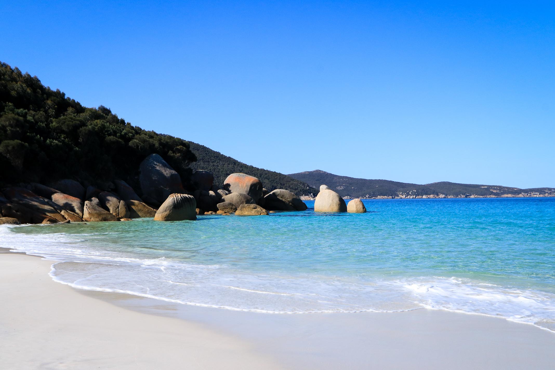 Exposed granite rocks on a calm white sand beach.