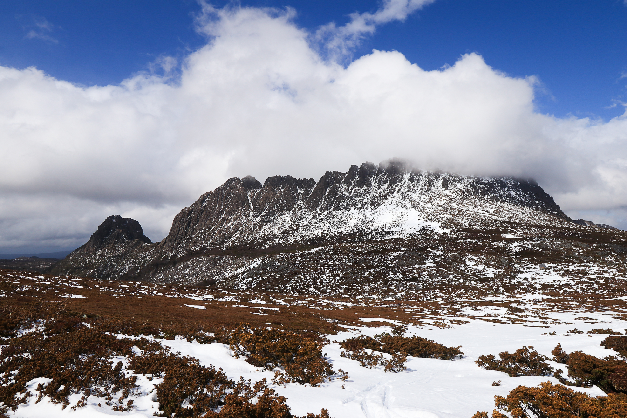 Iconic mountain holds on to snow, blue sky beyond