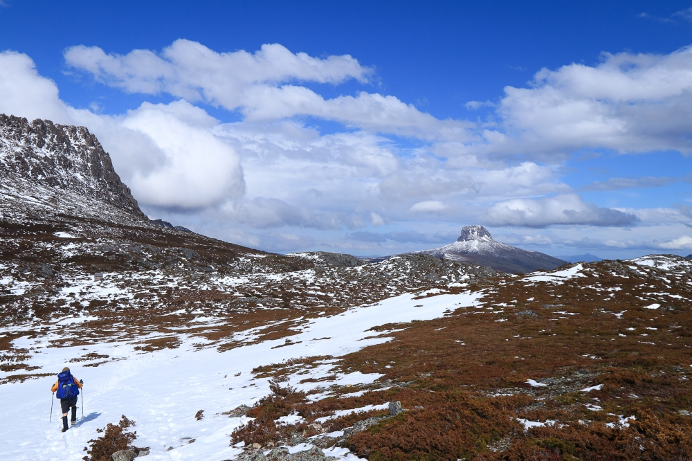 Blue sky and scattered clouds, hiker walks towards mountain on horizon.