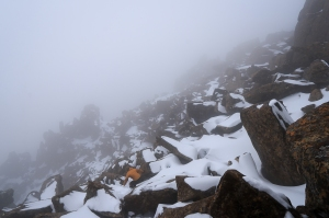 Mist hangs on snowy brown dolerite rock