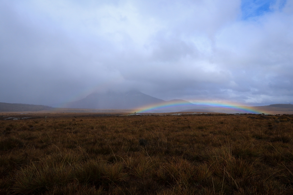 Low set rainbow in foreground of clouded mountain