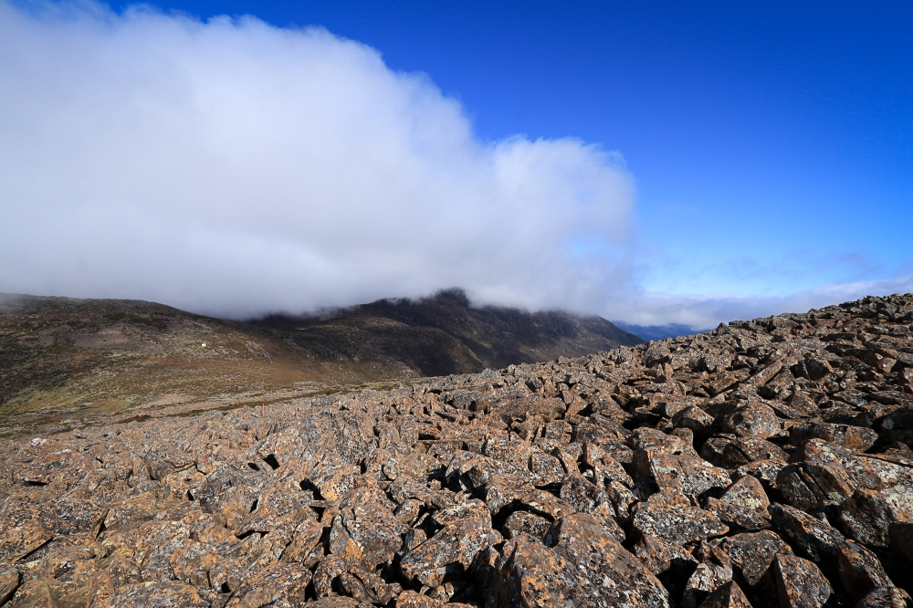 Fog hangs on mountain top, clear dolerite in foreground