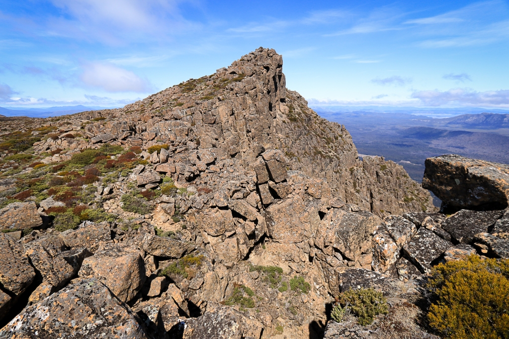 Boulders and scattered vegetation lead to mountain peak