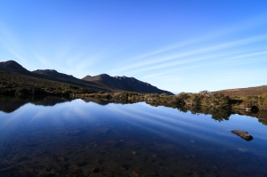 Blue sky reflected in mountain tarn, mountains in background.