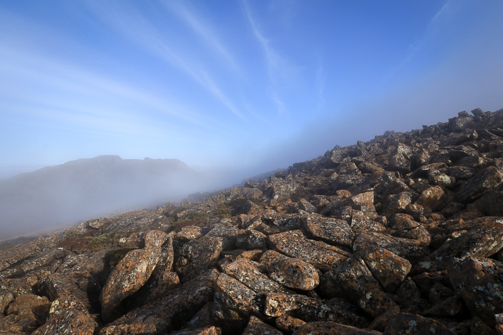 Fog distorts mountain background, foreground of dolerite boulders