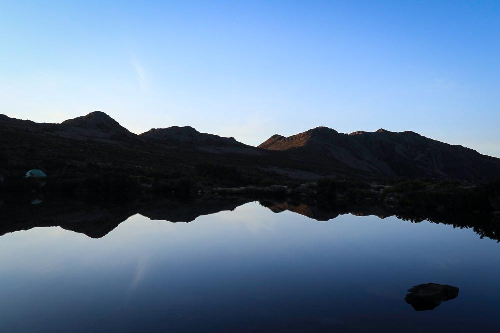 Mountain range silhouetted in lake.